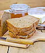 Stack Of Slices Of Rye Homemade Bread With A Knife On A Plate, Napkin, Loaf Of Bread, A Jar Of Honey On A Wooden Board