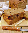 Stack Of Slices Of Rye Homemade Bread With A Knife And Rye Spikelet On Plate, Napkin, Loaf Of Bread On A Wooden Board stock photography