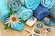 Stack Of Towels, Candles, Stones, Flowers On Mat Background. stock photo