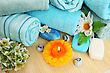 Stack Of Towels, Soaps, Candles, Stones, Flowers On Mat Background.