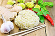 Stranded Rice Noodles With Garlic, Hot Red Pepper, Ginger, Basil And Broccoli, Chopsticks On A Wooden Boards Background stock photo
