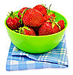 Strawberries In A Green Plastic Bowl On A Blue Checkered Napkin Isolated stock photo