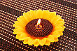 Sunflower Candle On Bamboo Background.