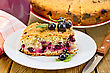 Sweet Piece Of Cake With Black Currant, Napkin, Cup, Knife On Background Wooden Plank