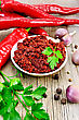 Tabasco Adjika In A White Cup, Fresh Red Peppers, Garlic, Peppercorns, Parsley On An Old Wooden Board stock photography