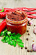 Tabasco In A Glass Jar, Fresh Red Peppers, Garlic, Peppercorns, Mustard Seeds On The Background Of The Old Wooden Boards