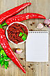 Tabasco In A White Cup, Fresh Red Peppers, Garlic, Peppercorns, Parsley, Notepad On An Old Wooden Board stock photo