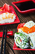 Tasty Rolls Served On Red Plate With Chopsticks On Wooden Table stock photo