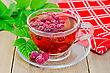 Tea With Raspberries In A Glass Bowl, Green Leaves Of Raspberry, Red Cloth On A Background Of Wooden Boards stock photography