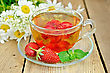 Tea With Strawberries In A Glass Cup, Mint, A Bouquet Of Camomiles On A Background Of Wooden Boards