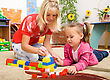 Teacher And Child Are Playing With Building Bricks In Preschool