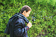 Teen With Ear-phone On Green Bush Background