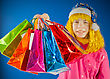 Teen Girl Holds A Variety Of Colorful Bags Against Blue Background stock photo