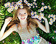 Teen Girl Lying In Grass With Flowers stock photo
