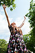 Teen Girl With Raised Hands Against Blue Cloudy Sky stock image