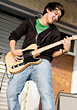 Musical Teenage Boy Playing Electric Guitar stock photo
