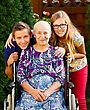 Teenager Grandchildren Visiting Their Old Disabled Grandmother stock photography