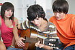 Teens Listening To Their Peer Play The Guitar stock image