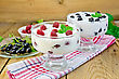 Thick Yogurt In Two Glasses With Raspberry And Black Currant On A Napkin, Berries And Mint On A Wooden Boards Background