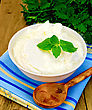 Thick Yogurt In A White Bowl, Parsley, Spoon, Napkin, Mint On The Background Of Wooden Boards