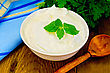Thick Yogurt In A White Bowl, Parsley, Spoon, Napkin, Mint On A Wooden Board stock image
