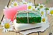 Three Bars Of Soap Pink, Green And White On A Piece Of Paper, Daisy Flowers On A Background Of Wooden Boards