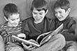 Three Brothers Reading Together stock photo
