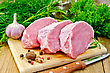 Three Chunk Of Pork, Garlic, Nutmeg, Parsley, Tarragon, Rosemary And Dill, Knife, Pepper On A Wooden Board stock photo