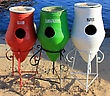 Three Colorful Recycle Trashcans On A Beach