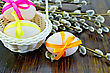 Three Easter Eggs Tied With Colored Ribbons, White Wicker Basket, Willow Twigs On A Wooden Board stock image