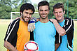 Three Football Players In Casual Clothes Posing For The Photo stock photography
