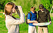 Three Friends Traveling. Girl Looking Through Binoculars stock photography