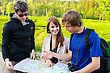 Three Friends Traveling, They Look At A Map stock photo