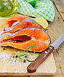 Seafood Three Pieces Of Trout With Rosemary And Coarse Salt, Pepper, Knife, Vegetable Oil, Lemon, Napkin On The Wooden Board stock photo