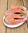 Three Pieces Of Trout In White Plate With Rosemary On A Wooden Boards Background stock photography