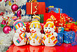 Three Snowmen In Front Of The Christmas Presents Over The Blue Background stock photo