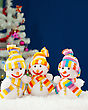 Three Snowmen In Front Of The Decorated White Evergreen Tree Over The Blue Background