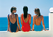 Three Women In Bathing Suits Sitting With Back To Camera stock image