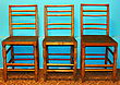 Three wooden chairs in front of azure color wall