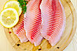Tilapia Fillets With Dill, Lemon And Pepper On A Wooden Board stock photo