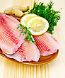 Tilapia Fillets With Lemon And Dill In Pottery, Ginger Root On The Background Of Wooden Boards stock photography