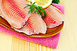 Tilapia Fillets With Lemon And Dill In A Pottery On A Pink Napkin On The Background Of Wooden Boards stock image