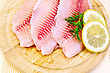 Tilapia Fillets With A Sprig Of Dill, Lemon Against A Wooden Board stock photo