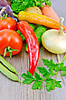 Tomatoes, Peppers Different, Cucumbers, Potatoes, Carrots, Bean Pods, Parsley, Onions On A Wooden Boards Background