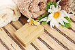 Towels And Olive Oil Soap With Aloe Vera, Flowers On Mat Background.
