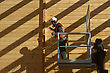 Tradesman Spray Painting The Wall Of A Wooden Industrial Building With Timber Preservative