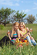 Playful Two Attractive Blonde With Wineglasses Sitting On A Grass stock photo