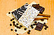 Two Bars Of Homemade Soap Beige And Brown, Chocolate Chips, Cinnamon, Coffee Beans On Old Paper On The Background Of Wooden Boards