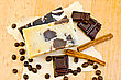 Two Bars Of Homemade Soap, Chocolate, Cinnamon, Coffee Beans On Old Paper On The Background Of Wooden Boards stock photo