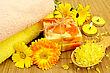 Two Bars Of Homemade Soap, Towels, Bath Salt In Wooden Spoon, Two Candles And Calendula Flowers On A Background Of Bamboo Napkins stock photo